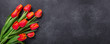 canvas print picture - Greeting Card for Mother's or Women's Day. Bouquet of red tulips on a dark stone table. Spring background. Top view. Copy space