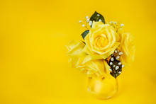 Yellow Rose Flowers Bouquet With Green Leaves In Glas Vase On Bright Yellow Background. Women's Day Or Mother's Day Festive Idea Backdrop With Copy Space. Floral Decoration. Selective Focus.