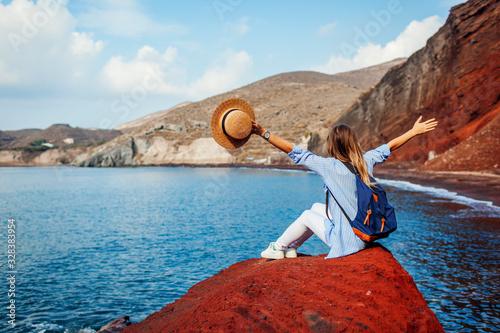 Fototapeta Traveler woman relaxing raising arms on rock on Red beach on Santorini island, Greece. Traveling and vacation obraz