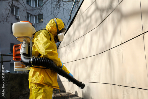 Photo Paramedic wearing yellow protective costume and mask disinfecting coronavirus wi