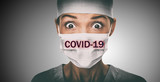 Covid-19 coronavirus text written over doctor surgical face mask Asian woman hospital worked scared shocked by Corona virus pandemic worried. Title on background.