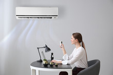 Young Woman Switching On Air Conditioner In Office