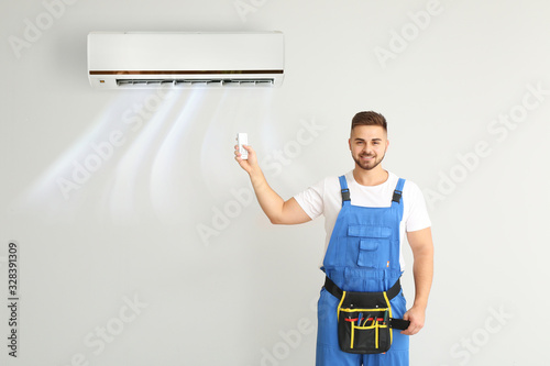 Photo Male technician switching on air conditioner on light wall