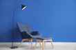 Leinwanddruck Bild - Modern armchair, stand and lamp near color wall