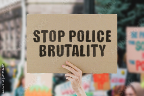 The phrase  Stop police brutality  on a banner in men's hand Canvas Print