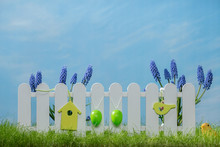 Spring Grass And Wooden Fence With Easter Eggs And Flower On Cloudy Sky
