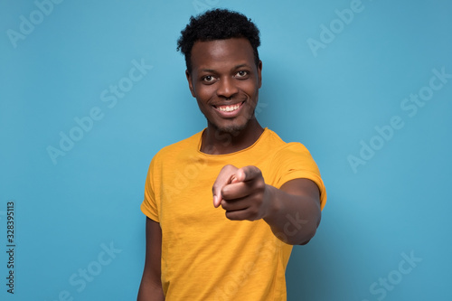 фотография Handsome young african man in yellow clothes pointing his finger at you