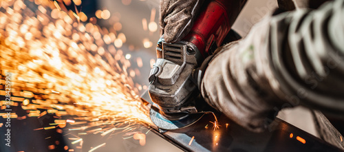 Fotografia Factory worker grinding a metal,close up