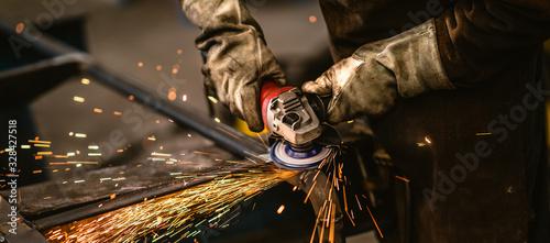 Fotografija Factory worker grinding a metal,close up