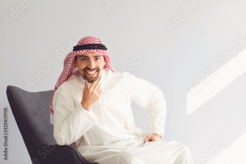 Arabic man portrait sitting on a chair on a gray background Wallpaper Mural