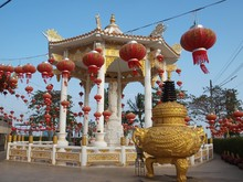 White Pagoda Decorated With Red Chinese Lanterns In The Courtyard Of A Buddhist Temple. Guanyin Or Guan Yin Sculpture Is Very Popular Bodhisattva Known As Avalokitesvara.