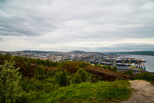 Top Distant View Of The City, Houses, Port, Ships And Water Of See, Lake Or River. Beautiful Summer Landscape With Cloudy Sky
