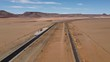Drone footage of a modern highway with a railway next to it in Namib desert