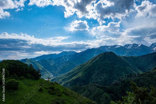 Fototapeta Almaty mountains with cloudy stormy clouds. Overcast - weather storm. Rain in mountains. obraz na płótnie