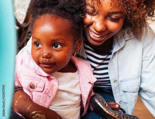 Photo adorable sweet young afro-american mother with cute little daughter, hanging at