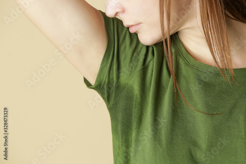 Close up image of woman in green t-shirt with sweat patch under armpit Wallpaper Mural