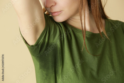Photo Close up image of woman in green t-shirt with sweat patch under armpit