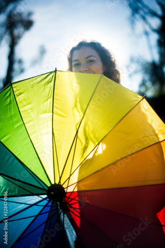 Photo Beautiful woman with umbrella of many colors in backlight on a sunny day