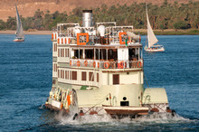 Sunny View Of Traditional Paddle Steamer Riverboat Churning Up The Waters With Traditional Felucca Boats Sailing In The Background On The Nile River In Egypt