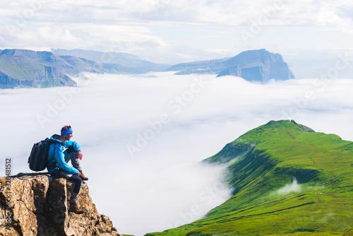 Fototapeta Hiker sitting on cliff, Mykines, Faroe Islands obraz