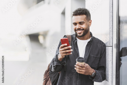 Young handsome men using smartphone in a city. Smiling student man texting on his mobile phone. Coffee break. Modern lifestyle, connection, business concept - 328484524
