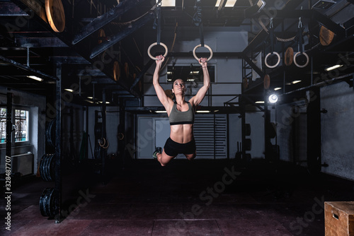 Young attractive muscular strong fit girl swinging on gymnastic ring heavy hardc Tablou Canvas