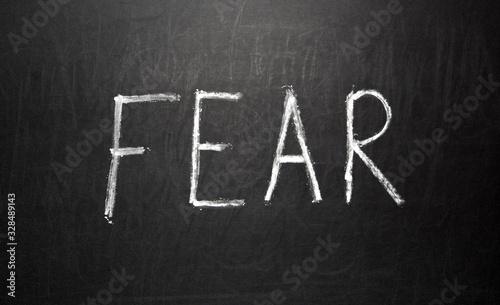 Text FEAR written in white chalk on a black chalkboard Canvas Print