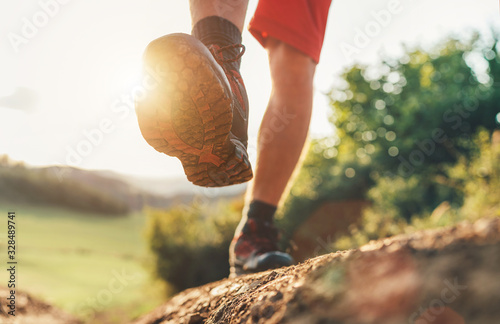 Fototapeta Trekking boot sole close up image traveler feet in trekking boots on mountain dirty path at summertime. obraz