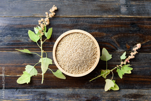 Obraz Organic raw brown quinoa seed (Chenopodium quinoa) in a bowl and quinoa plant on wooden background, healthy food, Top view - fototapety do salonu