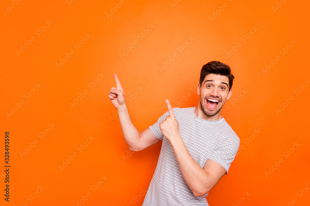 Fototapeta Photo of attractive guy hold hands fingers direct up empty space excited good mood sales person wear striped t-shirt isolated bright orange color background