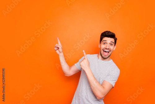Photo of attractive guy hold hands fingers direct up empty space excited good mood sales person wear striped t-shirt isolated bright orange color background