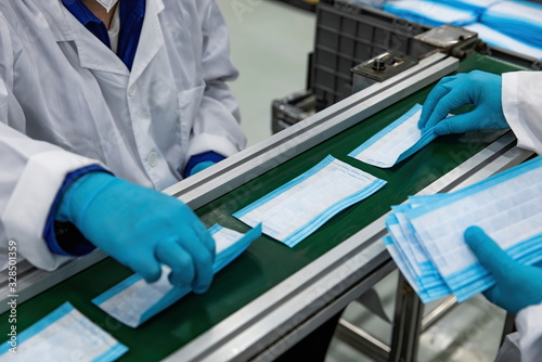 Fototapeta With the global spread of novel coronavirus pneumatia, the automatic production line of disposable medical masks makes masks continuously 24 hours to prepare for the epidemic