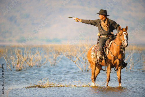 Cowboy on horseback on water and mountain background Canvas Print