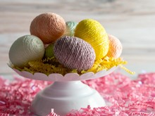 A White Platter Topped With String Decorated Easter Eggs And Yellow Paper Shred Sitting On A Surface Filled With Pink Paper Shreds And A Wooden Background.  Colorful Decoration For Easter.