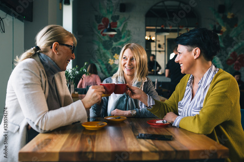 woman friends on coffee break at cafe, cheers with coffee