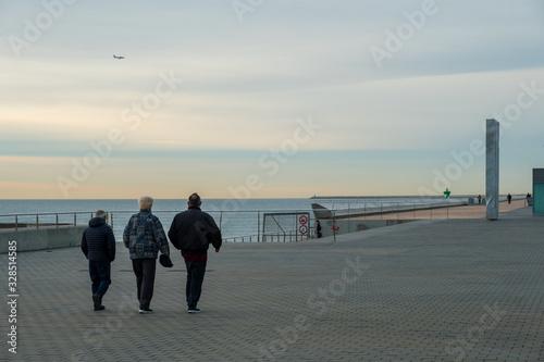 Abuelos caminando al amanecer por el paseo del mar. B Canvas Print