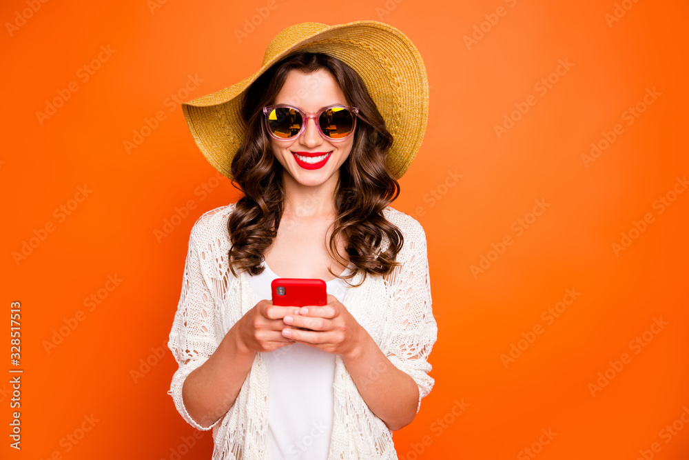 Fototapeta Photo of funny lady summer time holding telephone sending best friend photos from tropical ocean resort wear sun hat specs stylish beach cape isolated orange background