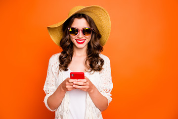 Photo of funny lady summer time holding telephone sending best friend photos from tropical ocean resort wear sun hat specs stylish beach cape isolated orange background