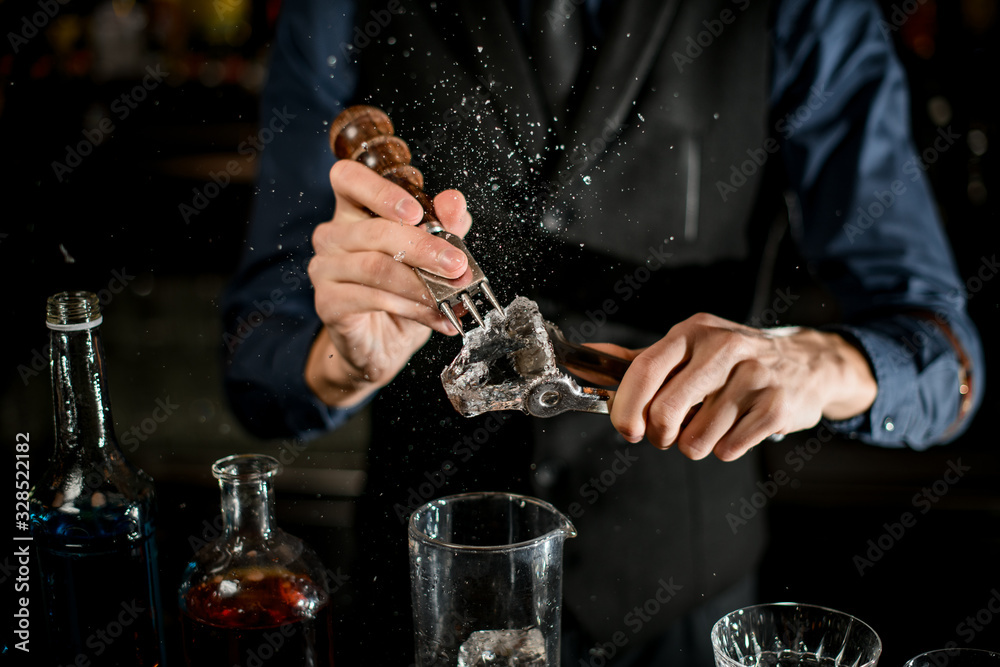 Fototapeta Bartender breaks the ice for a cocktail and the pieces fly apart.