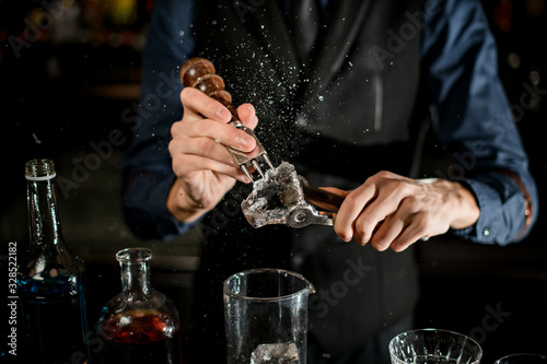 Fototapeta Bartender breaks the ice for a cocktail and the pieces fly apart. obraz