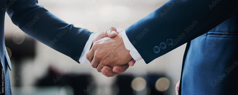 Fototapeta successful contract negotiate and handshake concept, two businessman shake hand with partner to celebration partnership, teamwork, business deal in room meeting after success communication, agreement