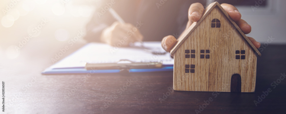 Fototapeta real estate, property and home owner signing contract concept, small wooden house model on office table with hand of woman buyer sign on rental agreement paper to rent above  mentioned residence