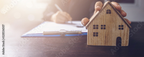 real estate, property and home owner signing contract concept, small wooden hous Canvas Print