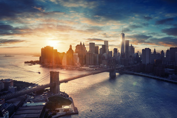 New York city at sunset with Manhattan. Aerial view to NYC with Brooklyn Bridge