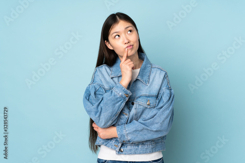 Fotografiet Young asian woman isolated on background having doubts while looking up