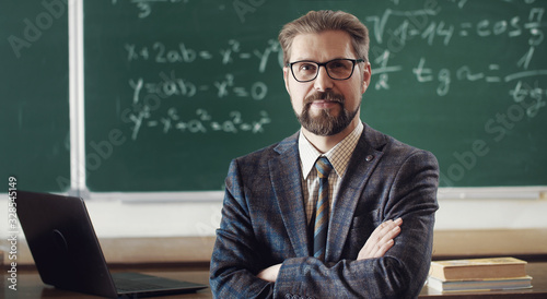 Stampa su Tela Portrait of smiling mature teacher in classic suit and eyewear standing cross-ar