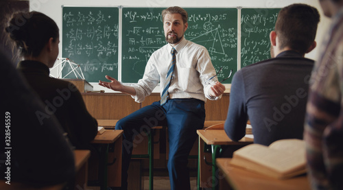 Back view of group of students attending math class and listening to teacher who Canvas Print