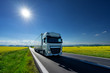 White truck driving on the asphalt road between the yellow flowering rapeseed fields under radiant sun in the rural landscape