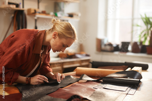 Cuadros en Lienzo Horizontal shot of young Caucasian woman preparing leather materials for new cra