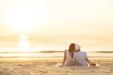 Couple Sit On Sand Looking Sun...